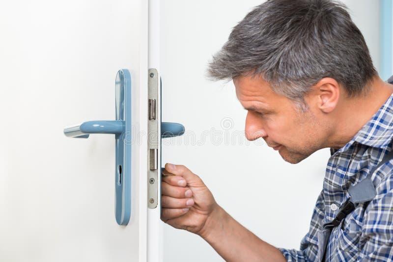 Κλειδαριά καθορισμού ξυλουργών στην πόρτα με το κατσαβίδι στοκ φωτογραφία