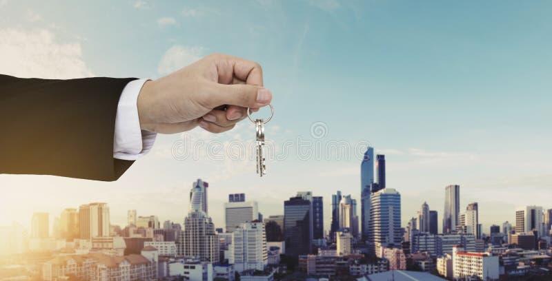 Κλειδιά εκμετάλλευσης χεριών με το υπόβαθρο πόλεων της Μπανγκόκ, το σπίτι αγοράς, την ακίνητη περιουσία και την έννοια ενοικίου σ στοκ εικόνες