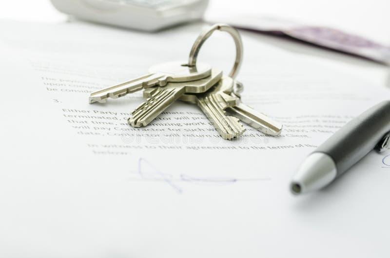 Κλειδιά σπιτιών σε μια σύμβαση της πώλησης σπιτιών στοκ εικόνα με δικαίωμα ελεύθερης χρήσης