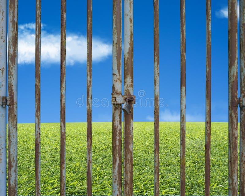 Κλειδωμένη σκουριασμένη πόρτα με το όμορφο τοπίο, πράσινο λιβάδι μπλε SK στοκ εικόνες