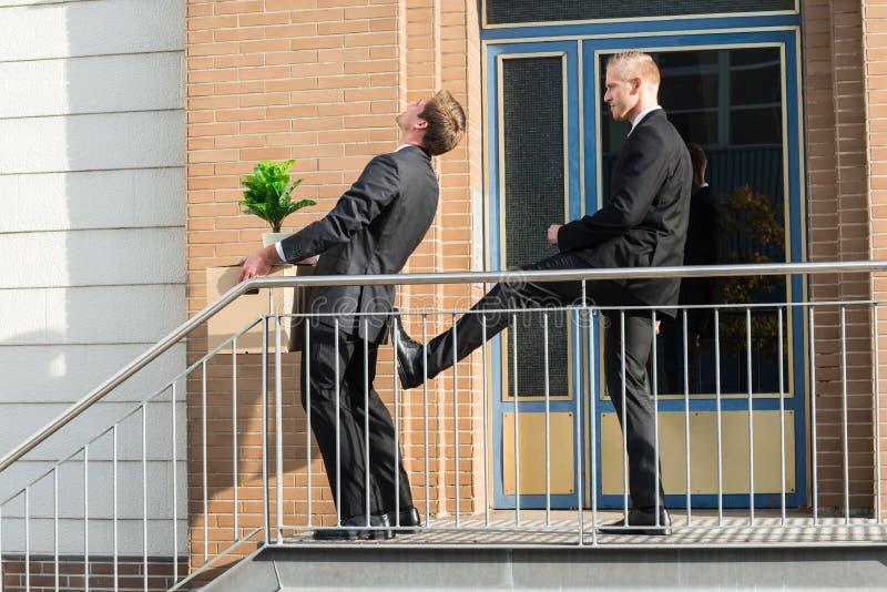 Κλωτσώντας υπάλληλος επιχειρηματιών με τις περιουσίες έξω από το γραφείο στοκ φωτογραφία με δικαίωμα ελεύθερης χρήσης