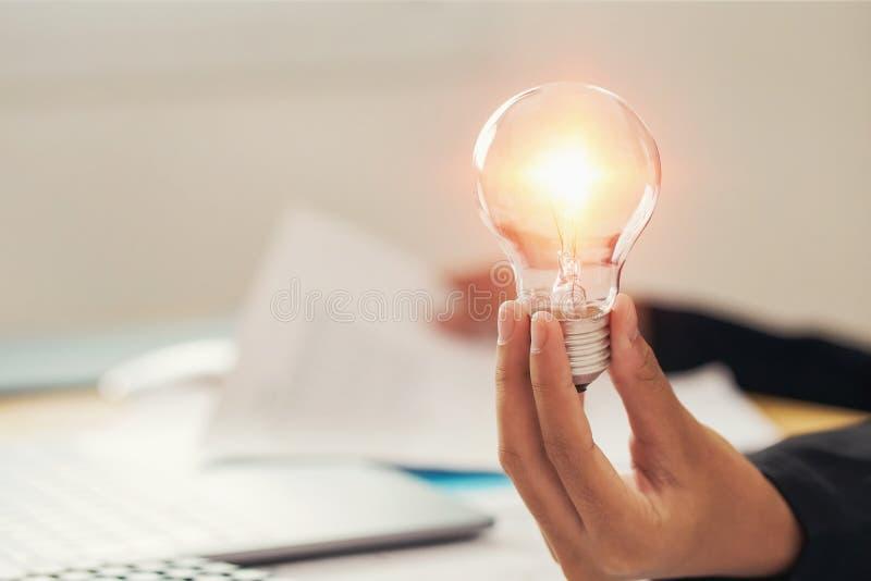 λάμπα φωτός εκμετάλλευσης χεριών έννοια ιδέας με την καινοτομία και την έμπνευση στοκ φωτογραφίες