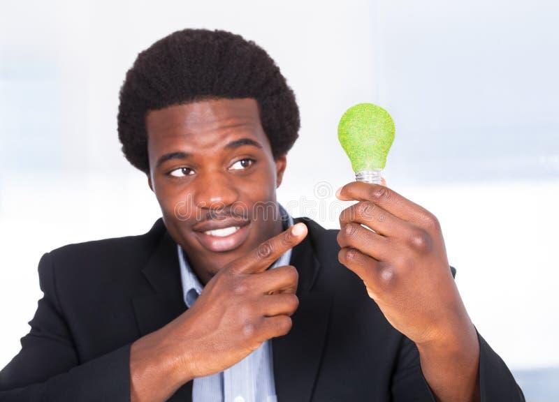 Λάμπα φωτός εκμετάλλευσης επιχειρηματιών με την πράσινη χλόη στοκ εικόνα