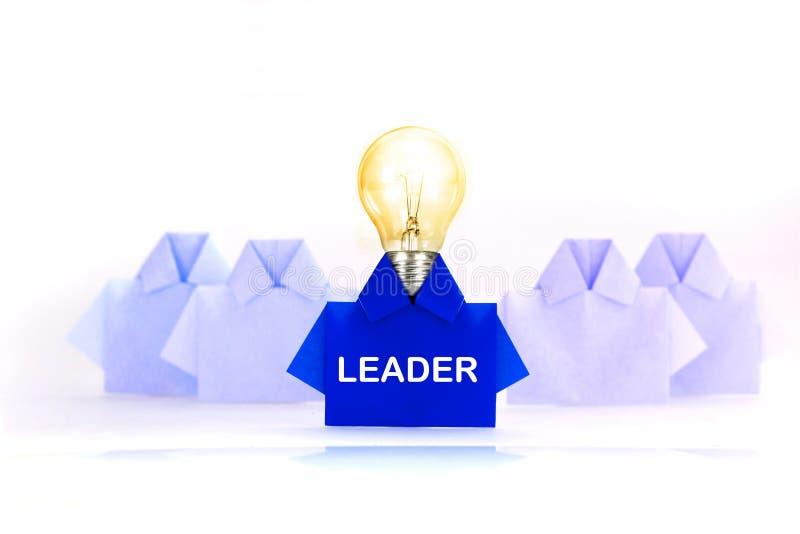 Λάμπα φωτός με τη λέξη ηγετών σε ένα μπλε μεταξύ του άσπρου origami shir στοκ φωτογραφία με δικαίωμα ελεύθερης χρήσης