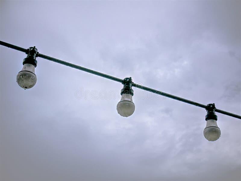 Λάμπες φωτός ενάντια στο νεφελώδη ουρανό τη βροχερή ημέρα στοκ φωτογραφίες με δικαίωμα ελεύθερης χρήσης