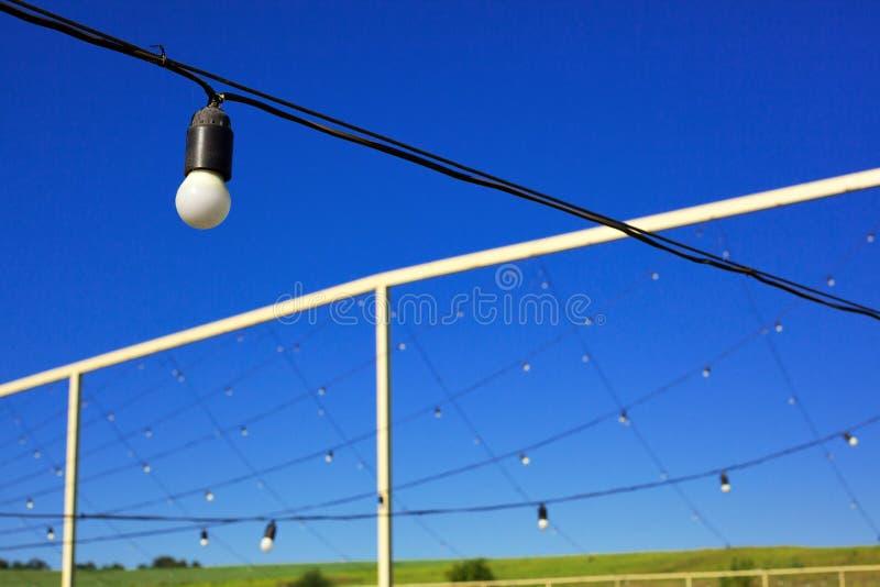Λάμπες φωτός που κρεμούν στη σειρά, μπλε ουρανός, πράσινος χορτοτάπητας στοκ φωτογραφίες με δικαίωμα ελεύθερης χρήσης