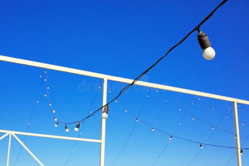 Λάμπες φωτός που κρεμούν στη σειρά, μπλε ουρανός, πράσινος χορτοτάπητας στοκ εικόνες