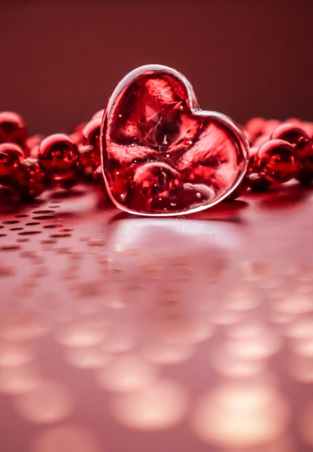 Λάμποντας διαφανής καρδιά και μια ομάδα κόκκινων χαντρών Υπόβαθρο ευχετήριων καρτών ημέρας του τέλειου βαλεντίνου Κάθετη εικόνα σ στοκ εικόνες