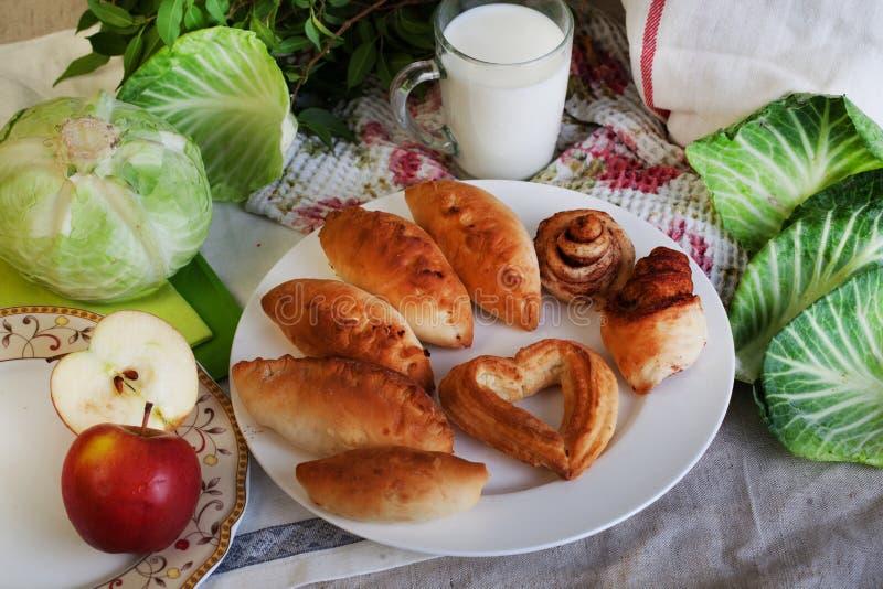 Λάχανο πιτών και κανάτα της ζωής γάλακτος ακόμα με μια περικοπή σημύδων, εγχώριο μαγείρεμα apptitnaya στοκ φωτογραφία