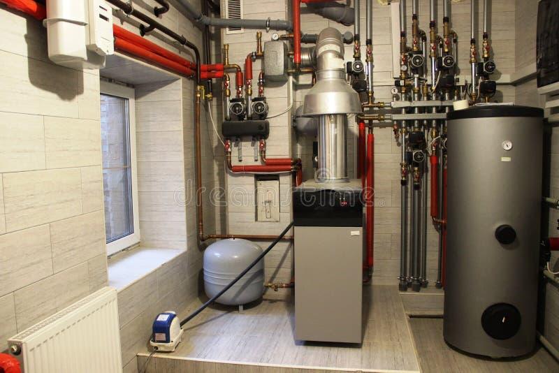 Λέβητας σπιτιών, θερμοσίφωνας, δεξαμενή επέκτασης και άλλοι σωλήνες newmodern ανεξάρτητο σύστημα θέρμανσης στο δωμάτιο λεβήτων στοκ εικόνα