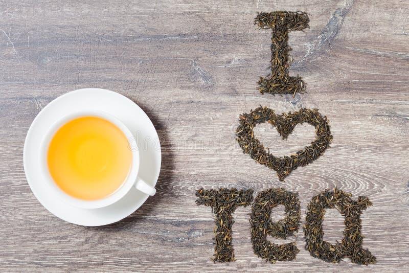 Λέξεις Ι τσάι αγάπης φιαγμένο από πράσινα φύλλα τσαγιού με ένα φλυτζάνι του τσαγιού στοκ φωτογραφία με δικαίωμα ελεύθερης χρήσης