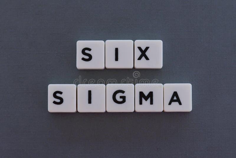 Λέξη έξι σίγμα φιαγμένη από τετραγωνική λέξη επιστολών στο γκρίζο υπόβαθρο στοκ φωτογραφίες με δικαίωμα ελεύθερης χρήσης