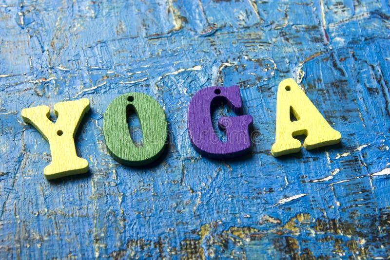 Λέξη γιόγκας φιαγμένη από ξύλινες ζωηρόχρωμες επιστολές στο εκλεκτής ποιότητας υπόβαθρο στοκ φωτογραφία