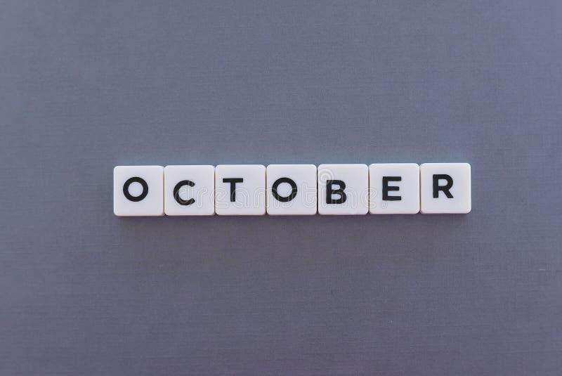 Λέξη Οκτωβρίου φιαγμένη από τετραγωνική λέξη επιστολών στο γκρίζο υπόβαθρο στοκ εικόνες