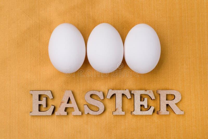 Λέξη Πάσχα, τρία άσπρα αυγά στο χρυσό κίτρινο υπόβαθρο μεταξιού στοκ φωτογραφία με δικαίωμα ελεύθερης χρήσης
