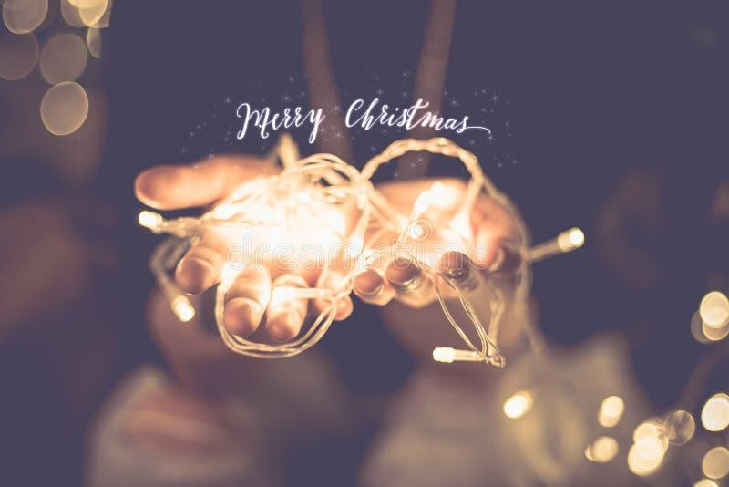 Λέξη πυράκτωσης Χαρούμενα Χριστούγεννας πέρα από το χέρι με την ελαφριά σειρά κομμάτων στοκ φωτογραφίες με δικαίωμα ελεύθερης χρήσης