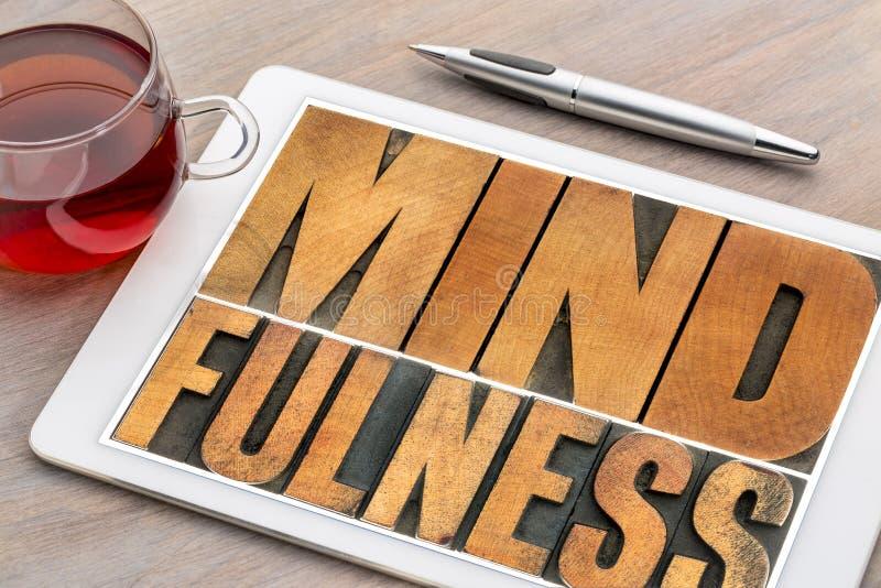 Λέξη Mindfulness στον ξύλινο τύπο στην ταμπλέτα στοκ εικόνα