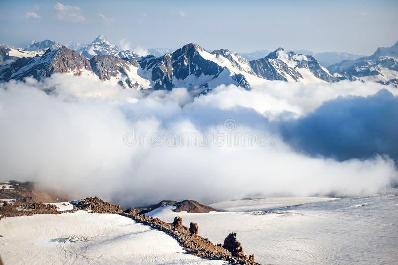 Λέσχες της ομίχλης και της κίνησης σύννεφων κατά μήκος της κλίσης του υποστηρίγματος Elbrus στοκ φωτογραφία
