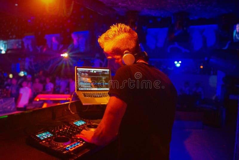 Λέσχη, disco DJ που παίζει και που αναμιγνύει τη μουσική για το πλήθος των ευτυχών ανθρώπων Νυχτερινή ζωή, φω'τα συναυλίας, φλόγε στοκ εικόνες