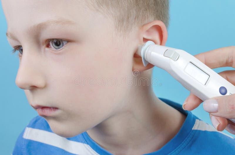 Λήψη της θερμοκρασίας με το θερμόμετρο αυτιών από το παιδί στοκ εικόνα με δικαίωμα ελεύθερης χρήσης