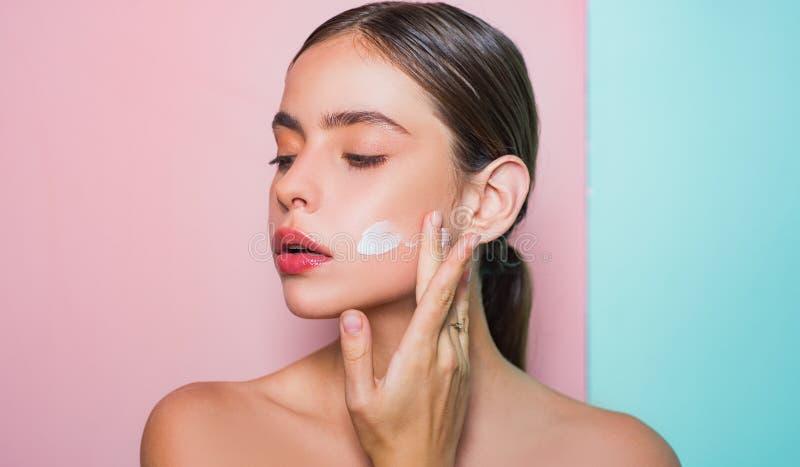 Λήψη της καλής προσοχής του δέρματός της Όμορφη κρέμα διάδοσης γυναικών στο πρόσωπό της Έννοια κρέμας δερμάτων Του προσώπου προσο στοκ φωτογραφία με δικαίωμα ελεύθερης χρήσης