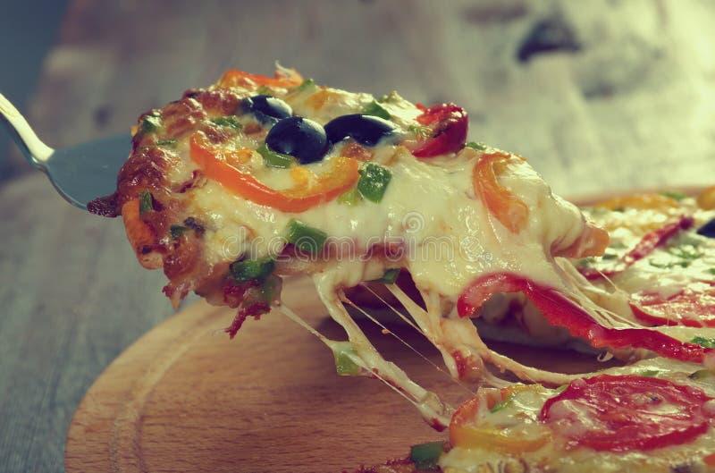 Λήψη της φέτας της πίτσας, λειωμένο στάλαγμα τυριών στοκ φωτογραφίες