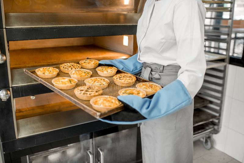 Λήψη των ψημένων κουλουριών από το φούρνο στοκ εικόνες