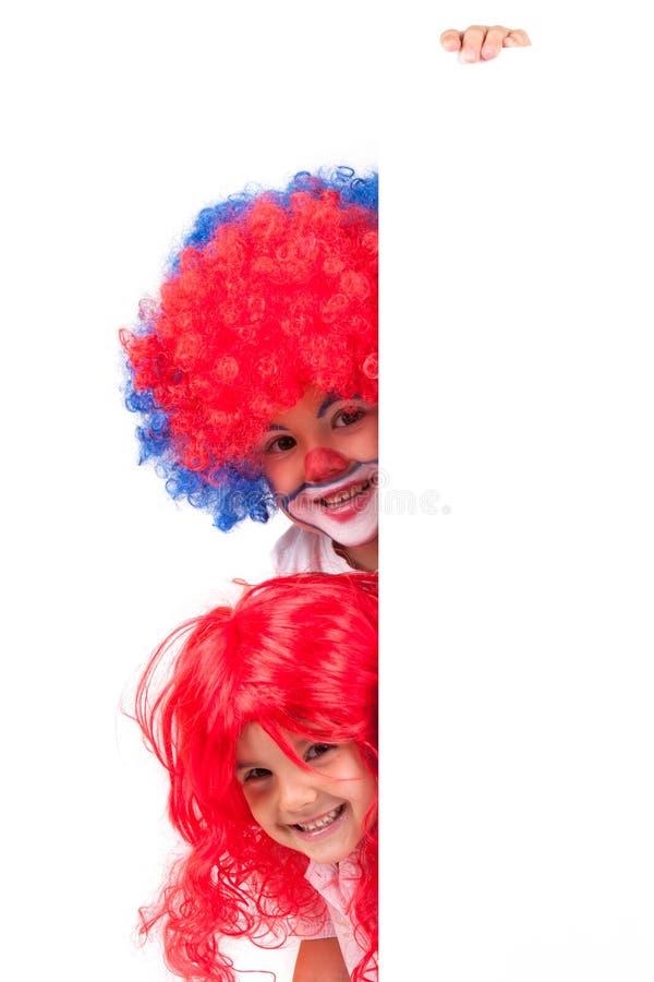 Λίγα αγόρι και μικρό κορίτσι κλόουν με μια κόκκινη περούκα στοκ φωτογραφία με δικαίωμα ελεύθερης χρήσης