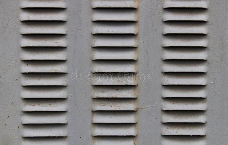 Λίγα κάγκελα εξαερισμού σιδήρου στην πόρτα σιδήρου Χάλυβας εξαερισμού αέρα Παλαιός εγκαταλειμμένος σκουριασμένος σταθμός μετασχημ στοκ φωτογραφία