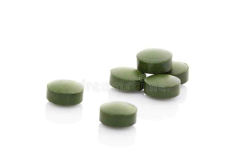 Λίγα πράσινα χάπια στο άσπρο υπόβαθρο. στοκ φωτογραφίες