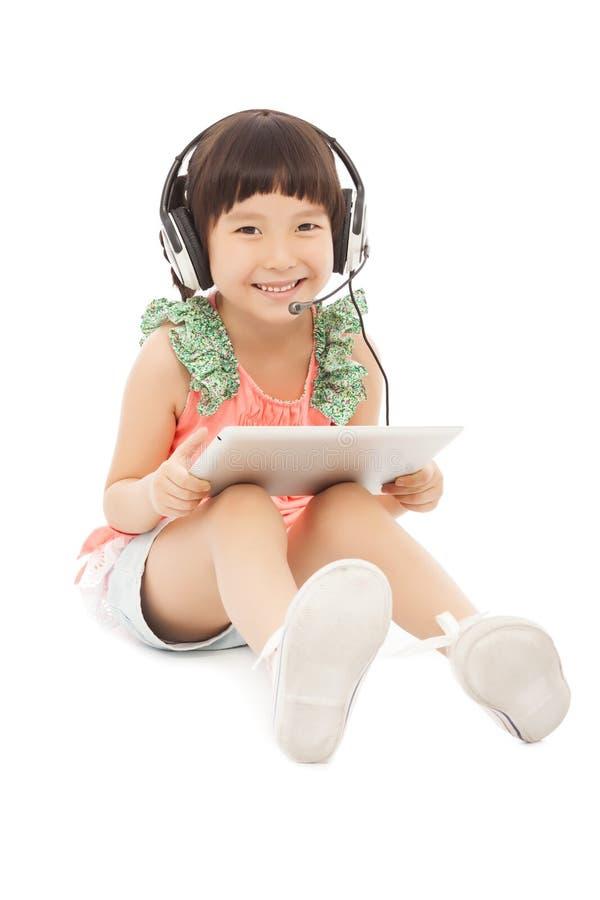 Λίγες συνεδρίαση και εκμετάλλευση κοριτσιών σπουδαστών μια ταμπλέτα με το ακουστικό στοκ φωτογραφία με δικαίωμα ελεύθερης χρήσης
