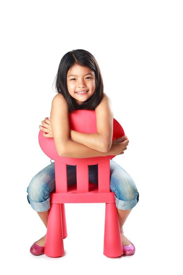 Λίγη ασιατική τοποθέτηση κοριτσιών στην καρέκλα στοκ φωτογραφίες με δικαίωμα ελεύθερης χρήσης