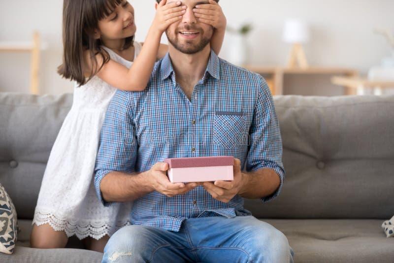 Λίγη κόρη που παρουσιάζει το κιβώτιο δώρων που κάνει την έκπληξη για την ευτυχή DA στοκ εικόνες με δικαίωμα ελεύθερης χρήσης