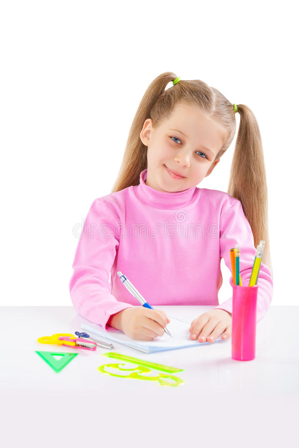 Λίγη μαθήτρια στο επιτραπέζιο γράψιμο στοκ εικόνες