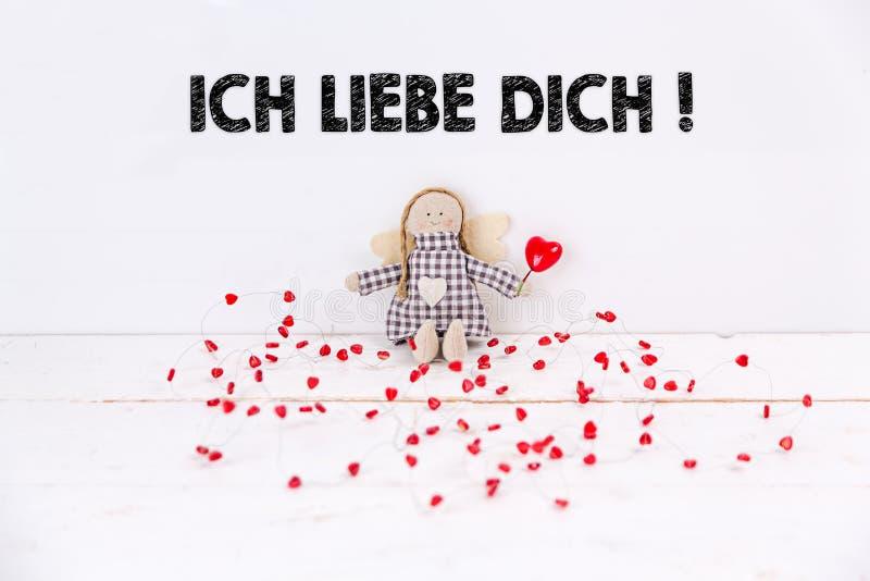 """Λίγη μαριονέτα με τις κόκκινες καρδιές που κάθονται στο άσπρο υπόβαθρο με το κείμενο """"Ich liebe dich """" Tranlation: """"Σ' αγαπώ """" στοκ φωτογραφίες"""