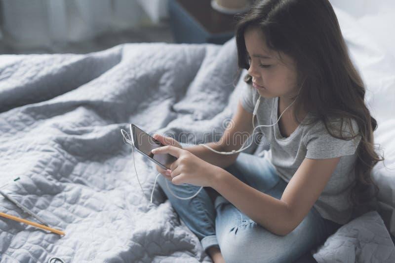Λίγη μαύρος-μαλλιαρή συνεδρίαση κοριτσιών στο κρεβάτι cross-legged και ακούοντας τη μουσική σε ένα γκρίζο smartphone το πρωί στοκ φωτογραφία