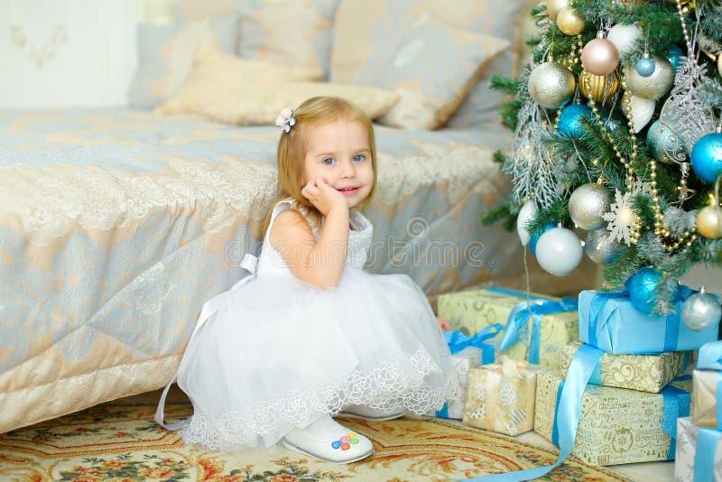 Λίγη ξανθή συνεδρίαση κοριτσιών παρουσιάζει πλησίον κάτω από το χριστουγεννιάτικο δέντρο στην κρεβατοκάμαρα στοκ φωτογραφία
