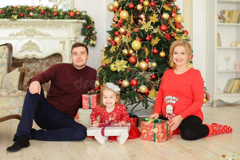 Λίγη ξανθή συνεδρίαση κορών με τον πατέρα και την έγκυο μητέρα κοντά στο χριστουγεννιάτικο δέντρο και την κράτηση των δώρων στοκ φωτογραφία με δικαίωμα ελεύθερης χρήσης