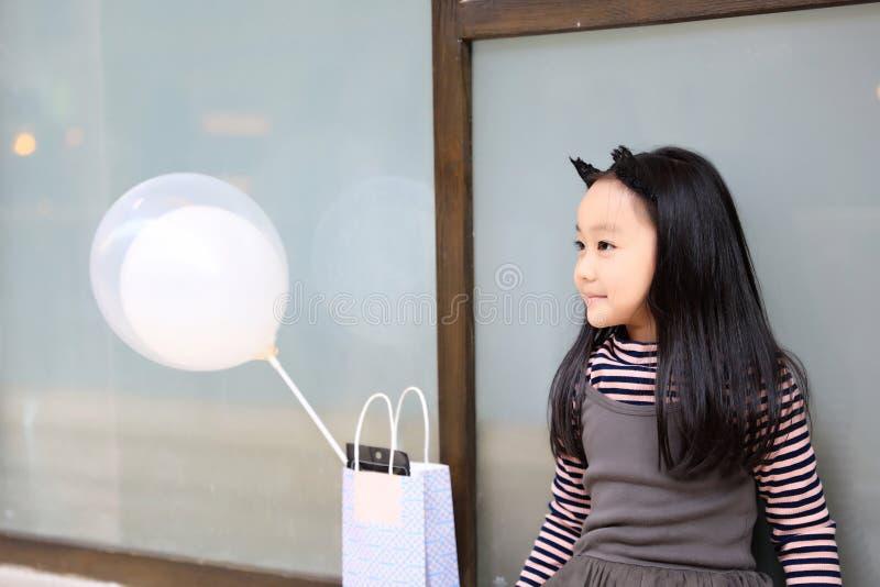 Λίγη πριγκήπισσα στην γκρίζα εκμετάλλευση φορεμάτων baloons στοκ φωτογραφία με δικαίωμα ελεύθερης χρήσης
