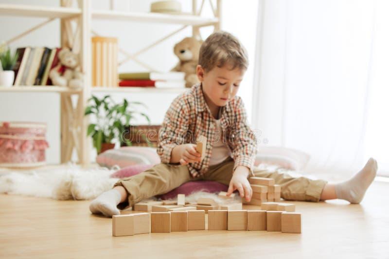 Λίγη συνεδρίαση παιδιών στο πάτωμα Όμορφο αγοριών με τους ξύλινους κύβους στο σπίτι στοκ εικόνα με δικαίωμα ελεύθερης χρήσης