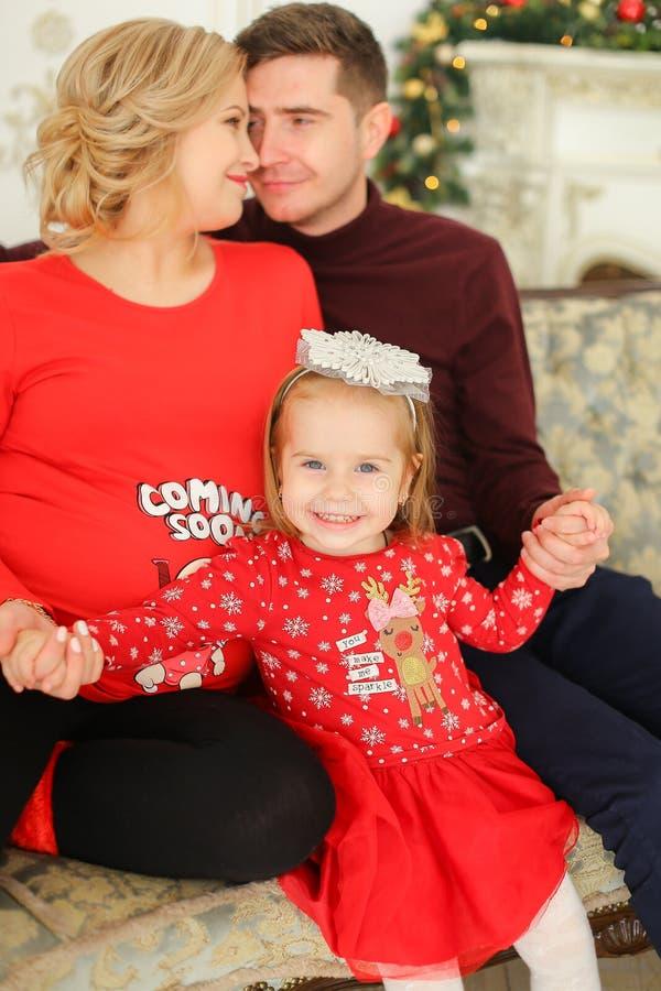 Λίγη συνεδρίαση παιδιών χαμόγελου θηλυκή με τον πατέρα και την έγκυο μητέρα πλησίον η εστία στοκ εικόνα με δικαίωμα ελεύθερης χρήσης