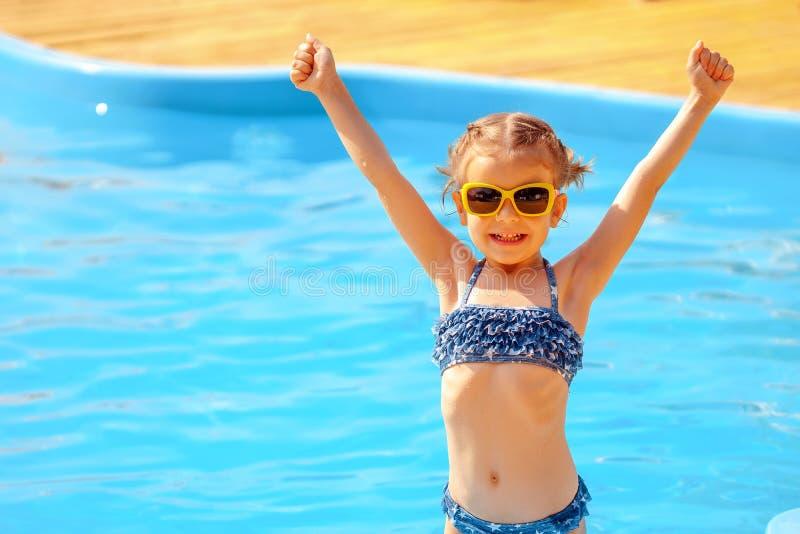 Λίγη χαριτωμένη εκμετάλλευση κοριτσιών δίνει επάνω κοντά σε μια πισίνα στοκ εικόνα με δικαίωμα ελεύθερης χρήσης