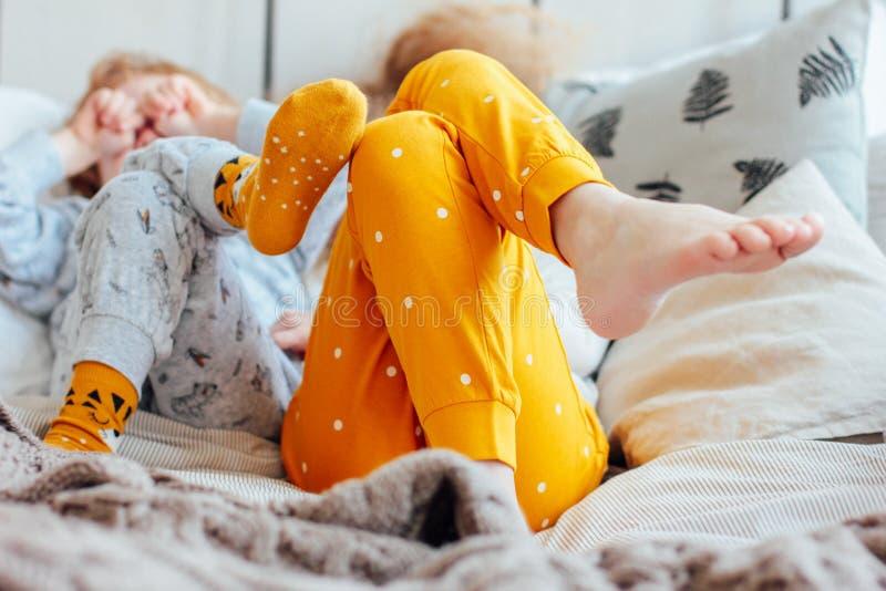 Λίγοι όμορφοι αδελφός και αδελφή στις πυτζάμες που βρίσκονται στο κρεβάτι, άνετο πρωί, εστίαση στα πόδια στοκ εικόνα με δικαίωμα ελεύθερης χρήσης