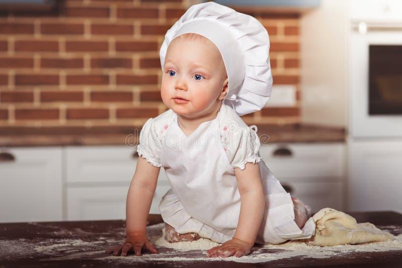 Λίγος αρτοποιός κοριτσάκι στο άσπρες καπέλο και την ποδιά μαγείρων στοκ εικόνες