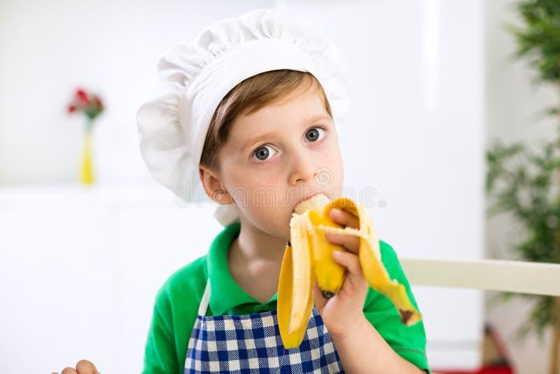 Λίγος αρχιμάγειρας που τρώει μια μπανάνα στοκ φωτογραφία με δικαίωμα ελεύθερης χρήσης