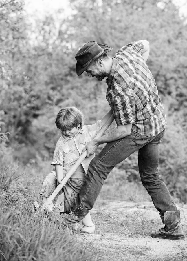 Λίγος αρωγός στον κήπο Χαριτωμένο παιδί στη φύση που έχει τη διασκέδαση με τον μπαμπά κάουμποϋ Βρείτε τους θησαυρούς Μικρό παιδί  στοκ εικόνες