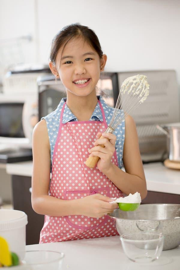 Λίγος ασιατικός χαριτωμένος αρχιμάγειρας που μαγειρεύει ένα αρτοποιείο στην κουζίνα στοκ εικόνες