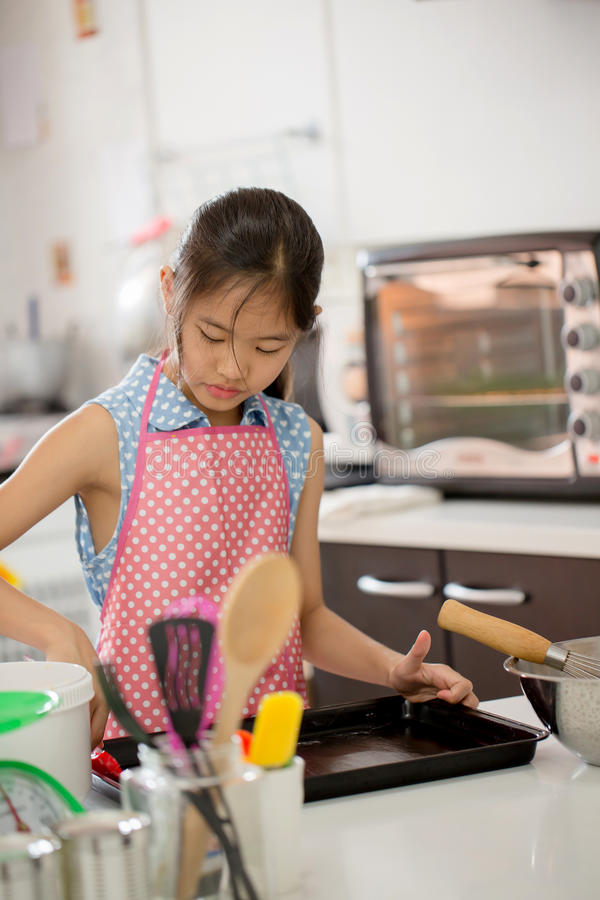 Λίγος ασιατικός χαριτωμένος αρχιμάγειρας που μαγειρεύει ένα αρτοποιείο στην κουζίνα στοκ εικόνα με δικαίωμα ελεύθερης χρήσης