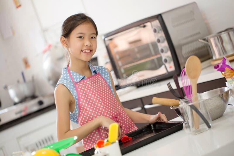 Λίγος ασιατικός χαριτωμένος αρχιμάγειρας που μαγειρεύει ένα αρτοποιείο στην κουζίνα στοκ φωτογραφίες με δικαίωμα ελεύθερης χρήσης