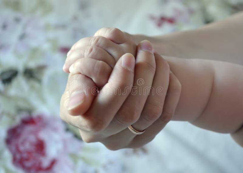 Λίγος βραχίονας μωρών σε ένα θηλυκό χέρι Θέμα της μητρότητας και της παιδικής ηλικίας, προστασία παιδιών στοκ φωτογραφία